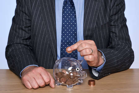 pennies: Photo of a banker sat at his desk putting coins into his piggy bank.