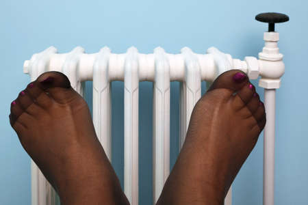 Photo of a woman's feet in stockings being warmed against an old traditional cast iron radiator.