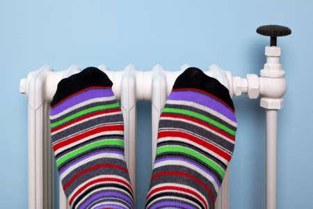 Foto di un piede della persona in calze a righe riscaldamento loro contro un vecchio radiatore tradizionale in ghisa.
