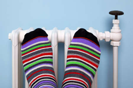 against: Photo of a persons feet in striped socks warming them against an old traditional cast iron radiator. Stock Photo