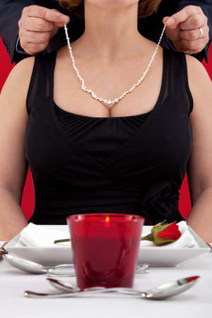 diamond necklace: Photo of a man putting a diamond necklace around the neck of his wife , who is sat at a table in a restaurant celebrating her birthday or their wedding anniversary.