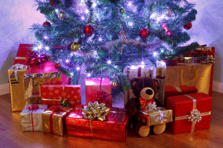 Photo of a Christmas tree with decorations and fairy lights surrounded by presents on a wooden floor. The teddy bear is generic and is not a known brand.
