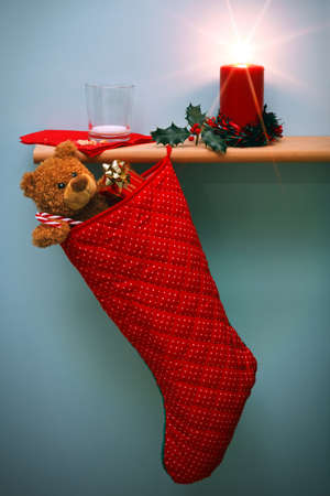 Photo of a Christmas stocking filled with presents and a candle surrounded by holly, also an empty glass of milk and crumbs from a mince pie, the star from the flame was done in camera using a filter. The teddy is generic and is not a brand name bear. photo