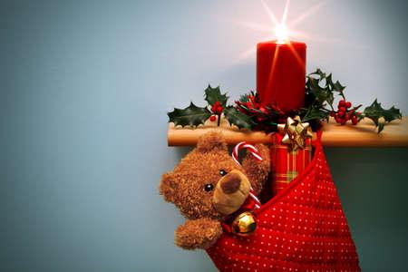 camino natale: Foto di una calza di Natale pieno di regali e una candela circondata da agrifoglio, l'orso ha una campana d'oro al collo, la star dal fuoco è stata fatta a porte chiuse, utilizzando un filtro. Il peluche è generico e non è un orso marca. Copia spazio a sinistra.