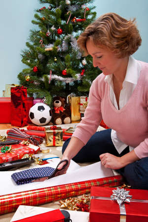 Photo of a woman sat on a rug at home wrapping her Christmas presents, Christmas tree in the background and gifts and paper around her. The teddy is generic and is not a brand bear. photo