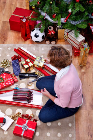 christmas wrapping: Overhead photo of a woman sat on a rug at home wrapping her Christmas presents. The teddy is generic and is not a brand bear. Stock Photo