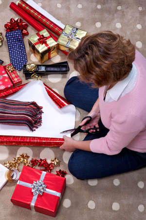 Photo of a woman sat on a rug at home wrapping a scarf for a Christmas present. photo