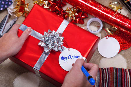 Photo of a woman writing Merry Christmas on a gift tag on a red present with silver ribbon and bow. Of course you could easily add your your message. photo
