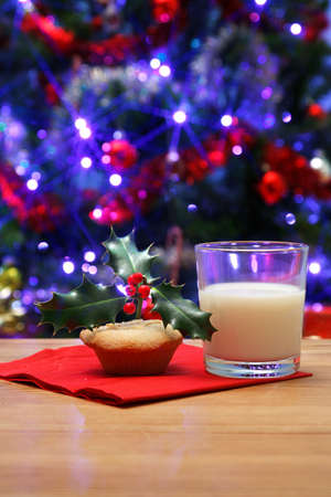 mince pie: Photo of a glass of milk and a mince pie with holly on top on a table, left out on Christmas eve for Santa, Christmas tree in the background with fairy lights and decorations.