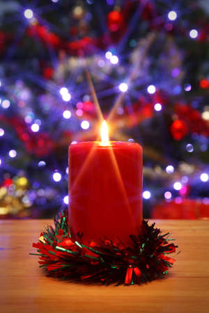 Photo of a Christmas candle with starburst, A Christmas tree with fairy lights is in the background, the star from the flame was created in camera using a filter. Stock Photo - 11329662