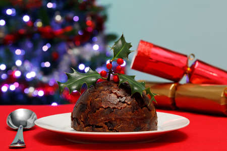 Photo of a Christmas pudding with holly on top with tree and crackers in the background. Stock Photo