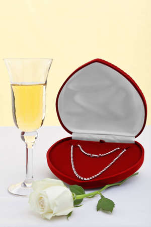 Photo of a diamond necklace in a heart shaped jewellery box with a glass of champagne and white rose. Good image for a wedding anniversary or Valentines theme. photo