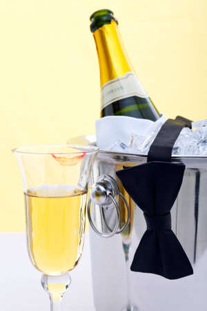 Photo of a bottle of chilled Champagne in an ice bucket with a black bow tie drapped over it and a glass with a red lipstick mark on.