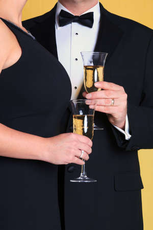 formal dress: Photo of a couple in black tie evening dress holding a glass of champagne.