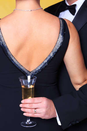 formal clothing: Photo of a couple in black tie evening wear, rear view of the womans back with the man holding a glass of champagne.