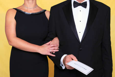 Photo of a couple in black tie evening wear, the man is holding an invitation. photo