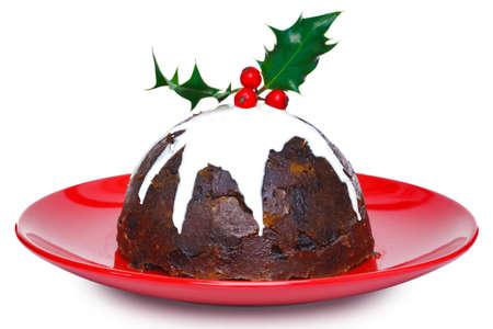 plum pudding: Foto di un budino cotto a vapore di Natale con crema e agrifoglio in alto isolato su uno sfondo bianco. Motion blur leggera la crema. Archivio Fotografico