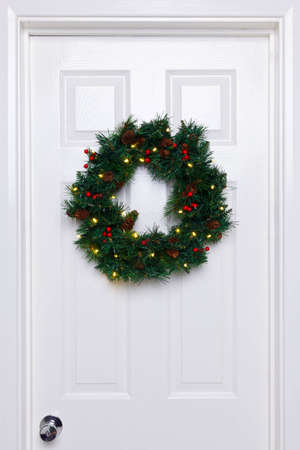 Photo of a Christmas wreath with lights hanging on a white front door. photo