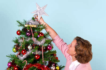 topper: Photo of a woman at home decorating her Christmas tree and finishing off by putting the star on top.