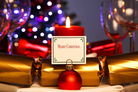 Photo of a Christmas dinner place setting and bauble card holder with decorated tree out of focus in the background. Lit by candlelight. photo