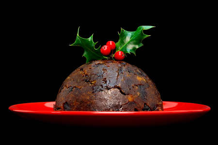 Photo of a Christmas pudding with holly on top isolated on a black background. Stock Photo