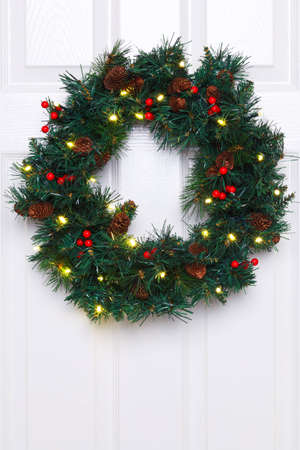 Photo of a Christmas wreath with fairy lights hanging on a white door. photo