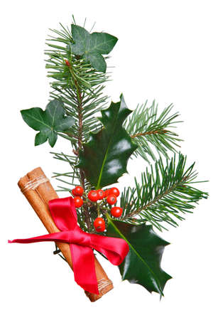 Photo of a Christmas decoration made with holly, red berries, spruce, ivy and a cinnamon stick with red bow, isolated on a white background. photo