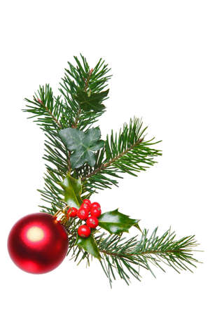 Photo of a Christmas decoration made with holly, red berries, spruce, ivy and a red bauble, isolated on a white background.
