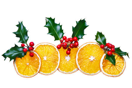 Photo of dried orange slices and holly with red berries arranged into a decorative Christmas image, isolated on a white background.  photo