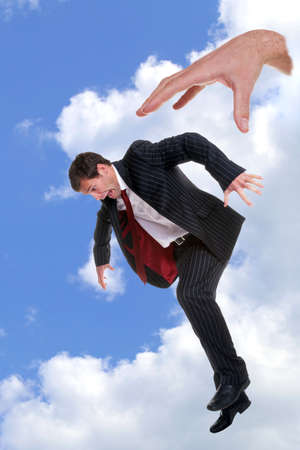 rejections: Concept photo of a businessman being dropped out of the sky by the hand of God, could be used to portray themes such as fear, fright, nightmare, refusal, dismissal, rejection, failure or disapproval. Plus any other you can think of.