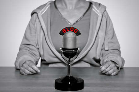 Woman sat at a desk with a retro microphone with the word BLOG on it. Image converted to black and white with BLOG on the mic sign in red to stand out. Stock Photo - 12194703