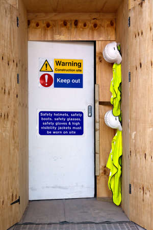 hard hats: Photo of the entrance to a construction site with health and safety notices, hard hats and high visibility jackets. Stock Photo