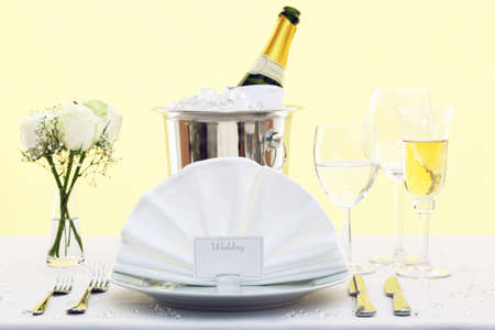 Photo of a wedding table place setting with place card and a bottle of chilled champagne in an ice bucket. photo
