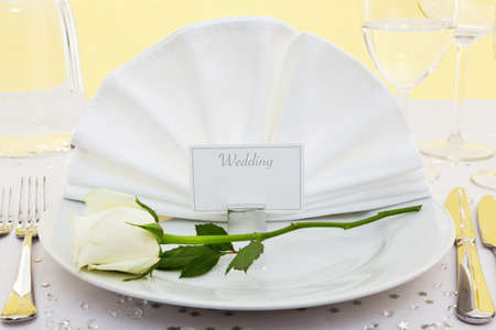 Photo of a table place setting for a wedding with a white rose on the plate. Stock Photo