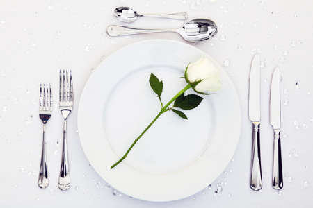 restaurant setting: Place setting with a white rose on the plate Stock Photo