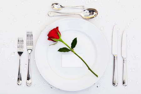 Photo of a table place setting with a red rose and blank card on the plate. Add your own message to the place card. photo