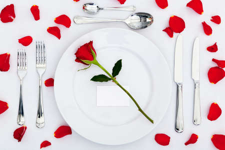 st  valentines day: Photo of a table place setting with a red rose and blank card on the plate plus rose petals on the tablecloth. Add your own message to the place card.