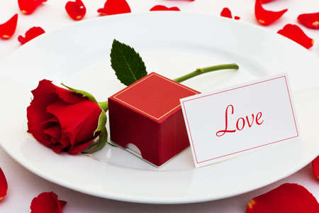 st valentines day: Photo of a red rose on a plate with a box for an engagement ring and a card with the word Love