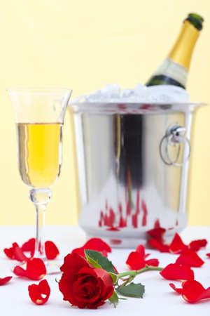 Foto di una rosa rossa e un bicchiere di champagne su una tovaglia di lino bianco con una bottiglia di champagne in un secchio di ghiaccio sullo sfondo. Archivio Fotografico - 12194649