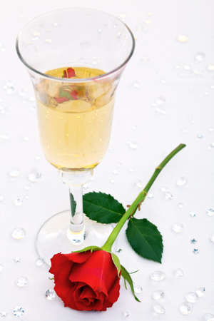 Photo of a single red rose and a glass of champagne with fake diamond table confetti. Focus is on the rose. photo