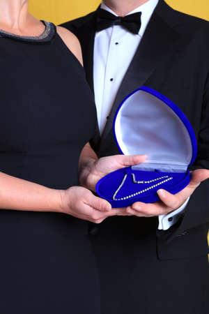 lazo negro: Foto de un hombre que llevaba corbata negra dando un regalo de un collar de diamantes a una mujer en un vestido negro.