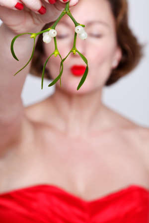 Photo of a woman in a red dress holding some mistletoe and kissing with her eyes shut.