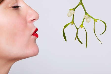 be kissed: Foto di una donna con gli occhi chiusi e il rossetto rosso in attesa di essere baciato sotto il vischio.