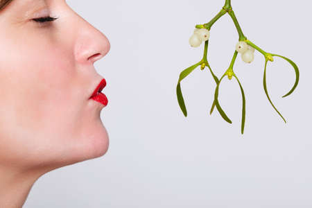be kissed: Photo of a woman with her eyes closed and red lipstick on waiting to be kissed under the mistletoe.
