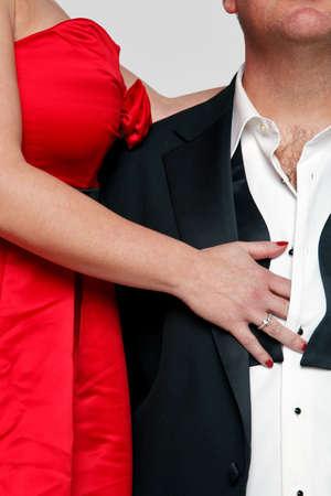 seducing: Foto di una donna in un abito rosso con unghie rosse sbottona la camicia di un uomo che indossa uno smoking e cravatta nera.