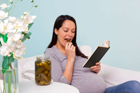 Photo of a pregnant woman at home sitting in an armchair with a craving for pickled gherkins. photo