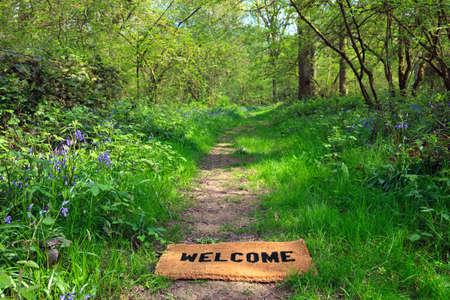 bienvenidos: Concepto foto de un felpudo de bienvenida en un sendero arbolado durante la primavera en formato horizontal.