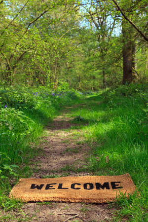 Concept photo of a Welcome doormat on a woodland footpath during springtime in vertical format. photo