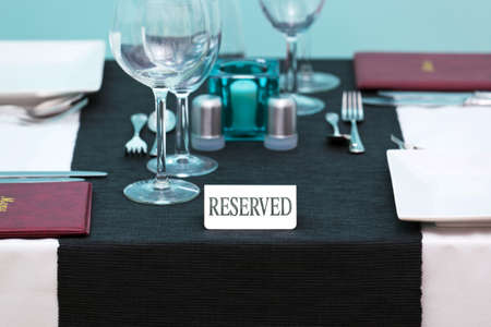 Photo of a Reserved sign on a restaurant table with menus on the side and place settings for two people. photo