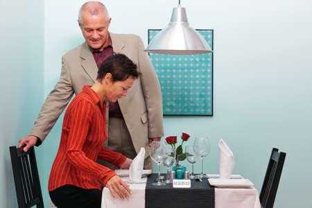 Foto van een volwassen paar aankomen en gaan zitten op hun gereserveerde tafel in een restaurant